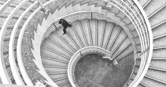 Businessman climbing spiral stairs | Evelyne Sieber / EyeEm/Getty Images