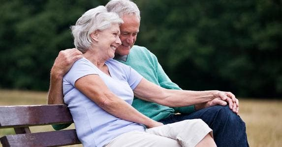 Senior couple sitting on bench in field | I love images/Getty Images