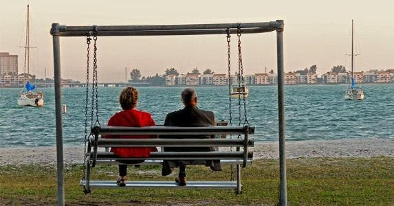 Retired couple sitting on swingset © AHPix/Shutterstock.com