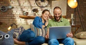 Laughing couple browsing on laptop in couch © StockLite/Shutterstock.com