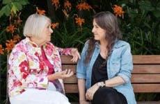 Two women sitting on a bench, talking | Allison Michael Orenstein/Getty Images