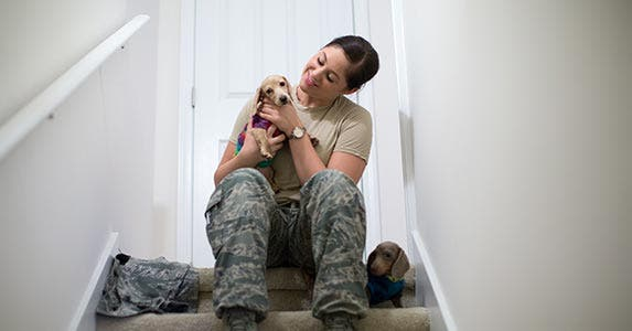 Service woman sitting on stairs holding a dog