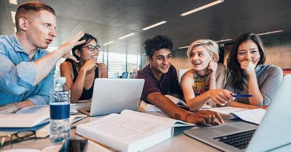Group study of college students in library | Jacob Lund/Shutterstock.com