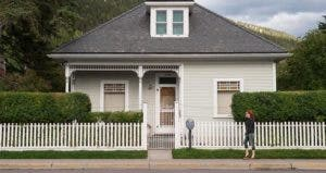 Woman walking past a house | John Elk III/Getty Images