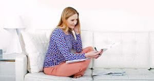 Woman on couch holding bills   Gary Houlder/Getty Images