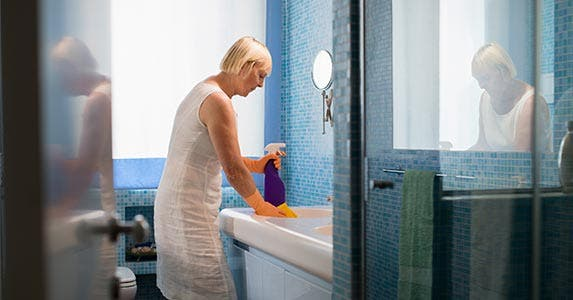 Woman cleaning bathroom sink