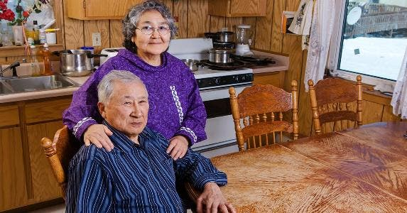 Senior couple sitting in kitchen | Kevin Smith/Getty Images