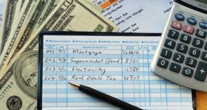 Balancing checkbook with money calculator bank statement © JohnKwan/Shutterstock.com