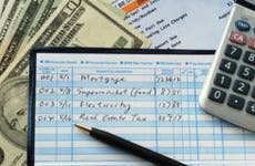 Balancing checkbook with money calculator bank statement © JohnKwan/Shutterstock.com