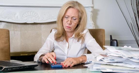 Woman using a calculator, budgeting © iStock