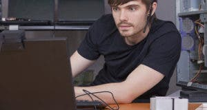 Male programmer with headset working on laptop computer © Edw/Shutterstock.com