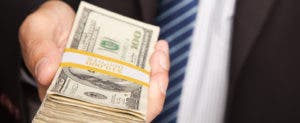 Business man handing over stack of one hundred dollar bills © Andy Dean Photography/Shutterstock.com