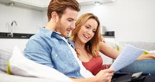 Couple looking over document on couch © Monkey Business Images/Shutterstock.com