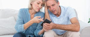 Worried couple looking at a calculator with bills in front of them © wavebreakmedia/Shutterstock.com