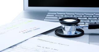 Medical bills, stethoscope on laptop © Gordon Swanson/Shutterstock.com