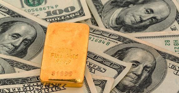 Gold bar on top of hundred dollar bills © Lisa S./Shutterstock.com