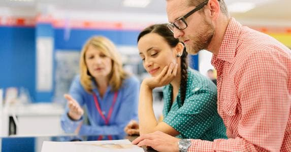 Salesperson explaining terms on document to couple customers © iStock