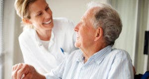 Elderly man speaking to a nurse © iStock