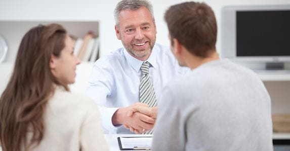 Male adviser shaking hands with client couple © iStock