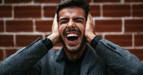 Man holding his ears while screaming © iStock