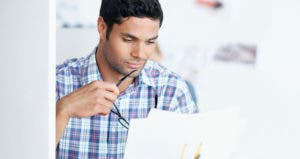 Young man overlooking paperwork at his desk © iStock