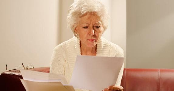 Senior woman scrutinizing her paperwork © iStock