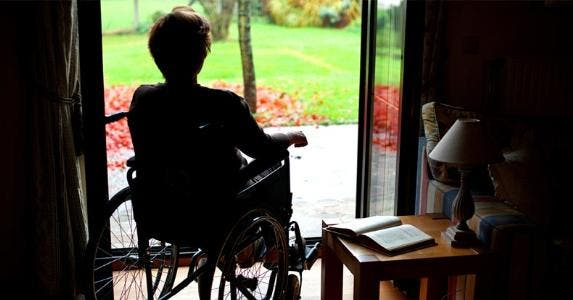 Senior woman in wheelchair looking out of window © iStock
