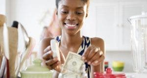 Young woman adding dollar to money jar in kitchen | Blend Images – JGI/Jamie Grill/Brand X Pictures/Getty Images
