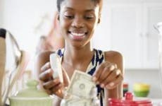 Young woman adding dollar to money jar in kitchen   Blend Images – JGI/Jamie Grill/Brand X Pictures/Getty Images