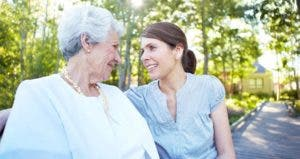 Elderly mother and adult daughter sitting outdoors © iStock