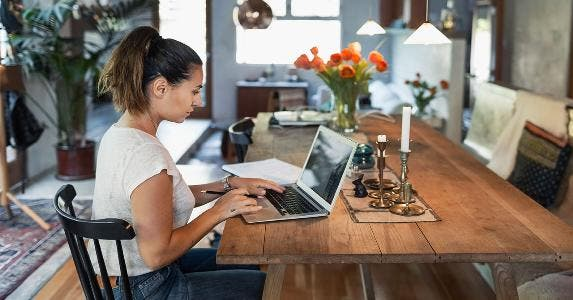 Woman sorting out finances on her laptop at home | Maskot/Getty Images