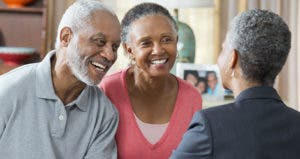 Older couple shaking hands with adviser in home | Ariel Skelley/Blend Images/Getty Images