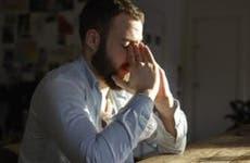Man pinching bridge of nose | Aleli Dezmen/Getty Images