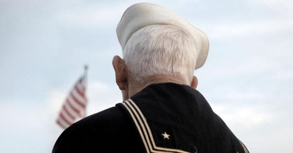 Senior veteran looking at American flag | EyeJoy/E+/Getty Images
