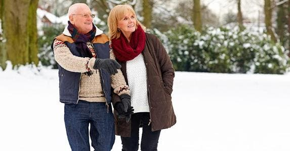 Mature couple walking outdoors in snow © iStock