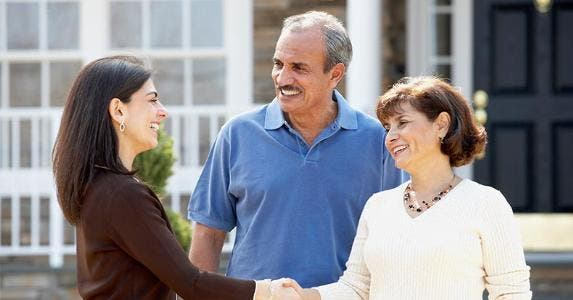 Mature couple shaking hands with real estate agent in front of house | Ariel Skelley/Getty Images