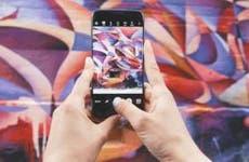 Woman holding smartphone taking photo of wall graffiti art | Patrick Tomass/Unsplash