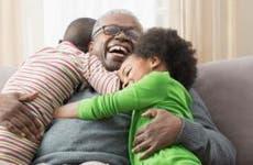 Grandfather hugging grandchildren | KidStock/Getty Images