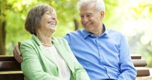 Laughing senior couple sitting on bench outdoors   alvarez/Vetta/Getty Images