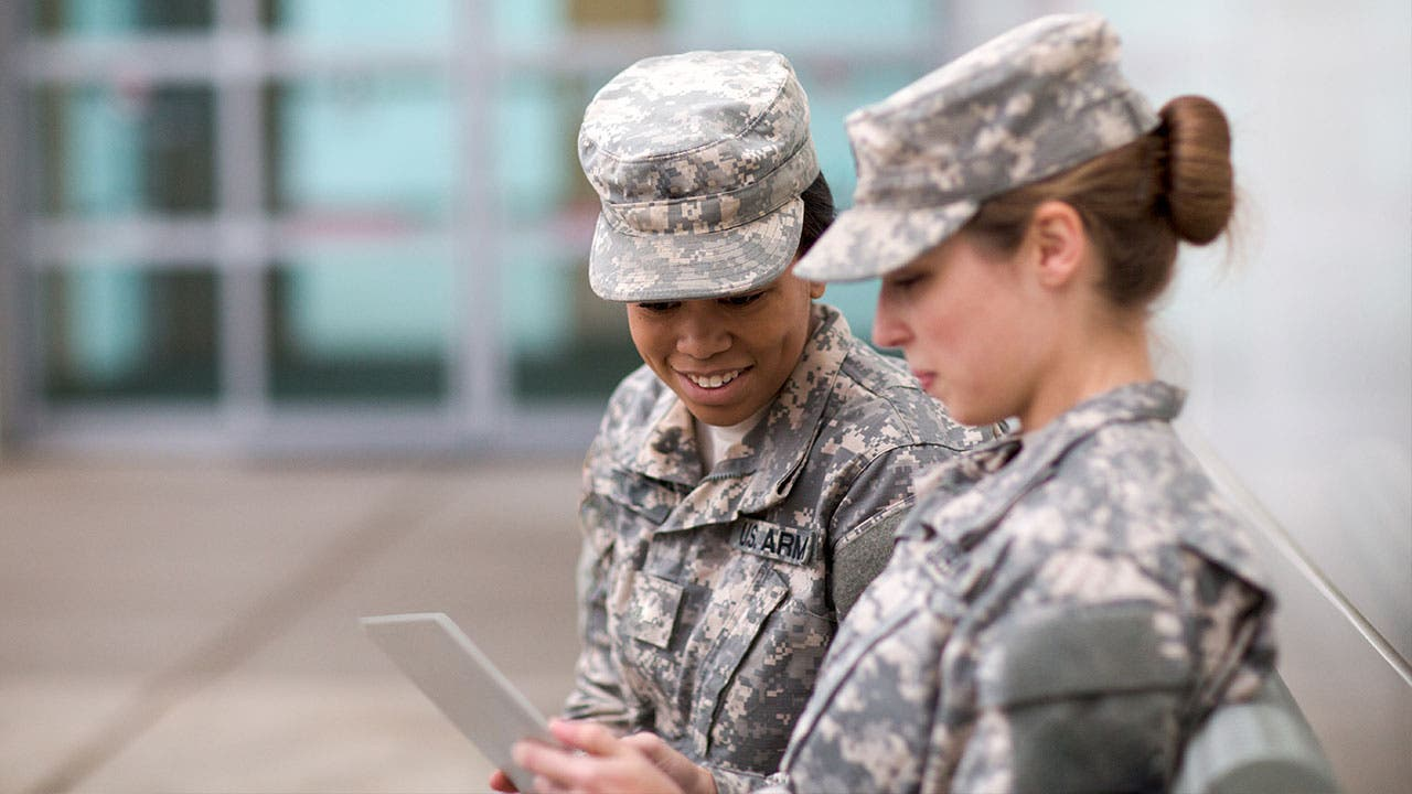 Two military women browsing tablet computer