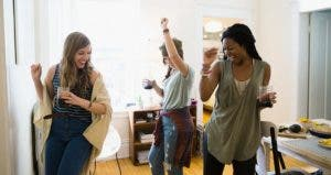 Three women dancing together in a room, celebrating