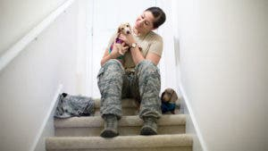 Servicewoman sitting on stairs holding dog