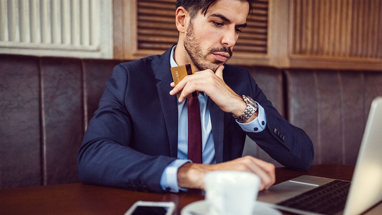 Man wearing suit holding credit card looking at laptop