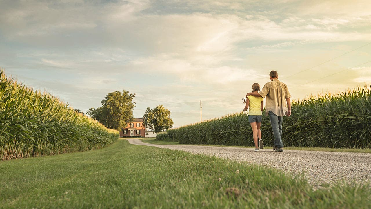 Couple walking toward rural home