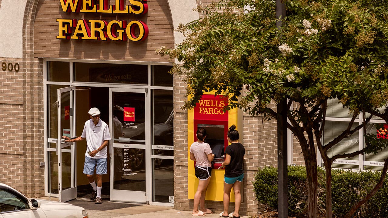 Customers use an ATM in front of a Wells Fargo branch.