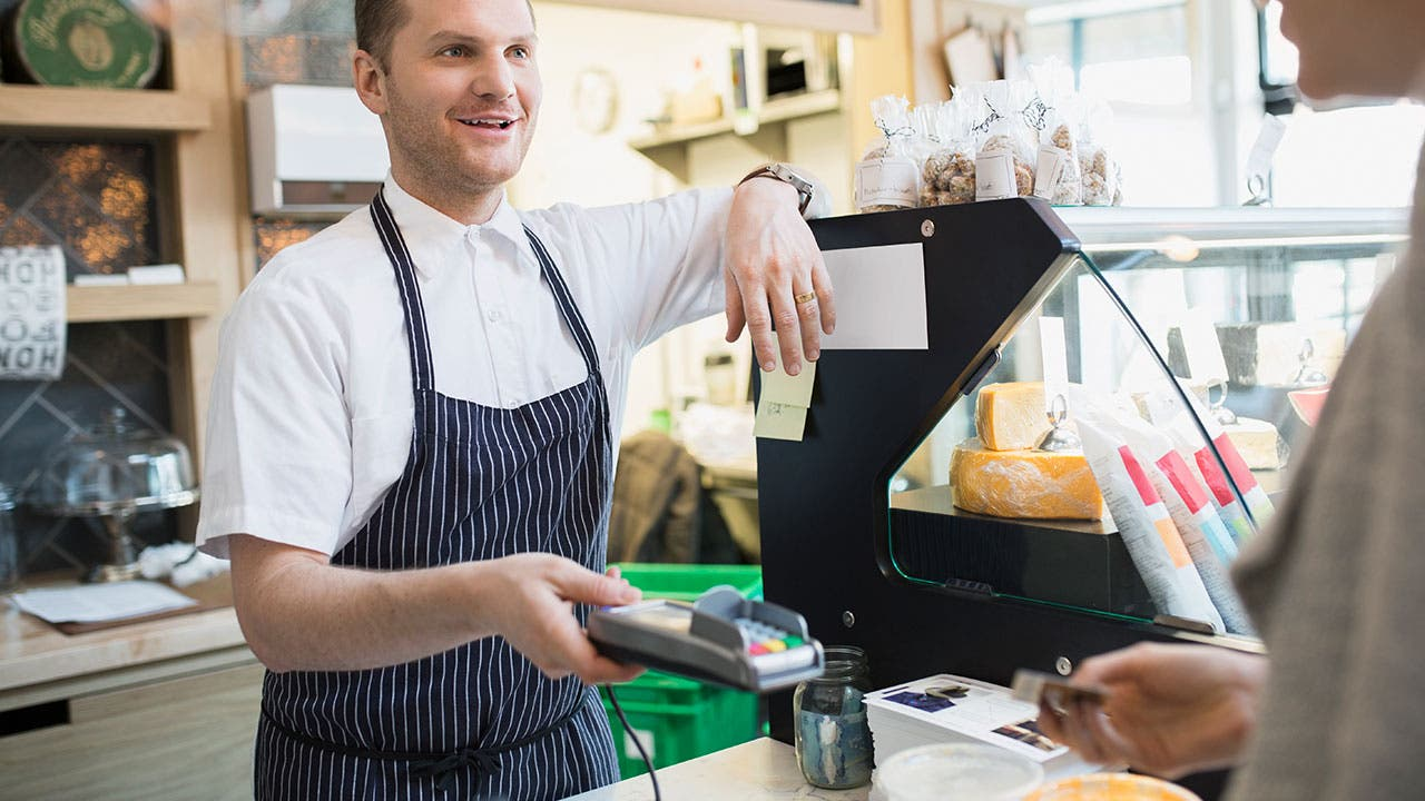 Clerk at deli handing credit card reader to customer