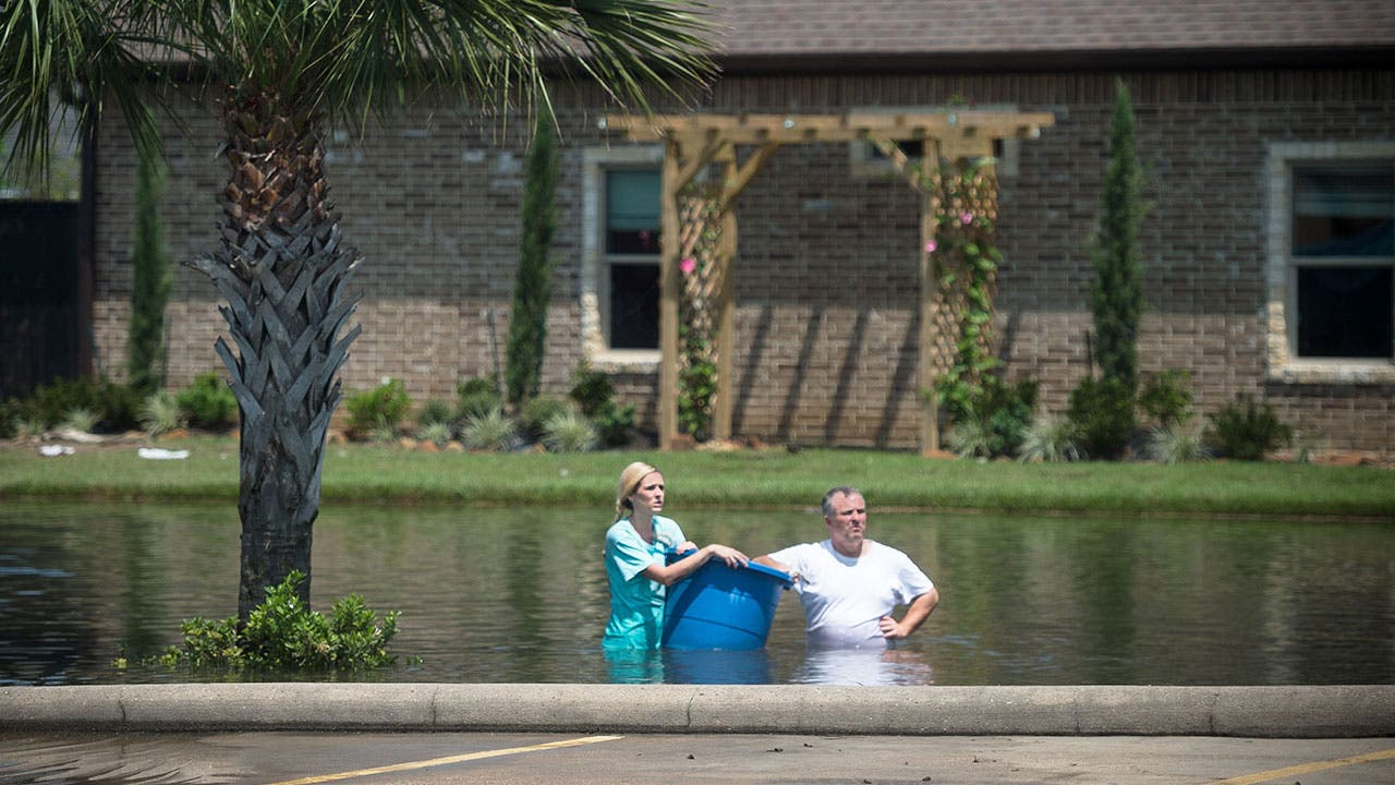 A couple wading in floodwaters