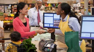Woman at grocery store handing credit card to cashier