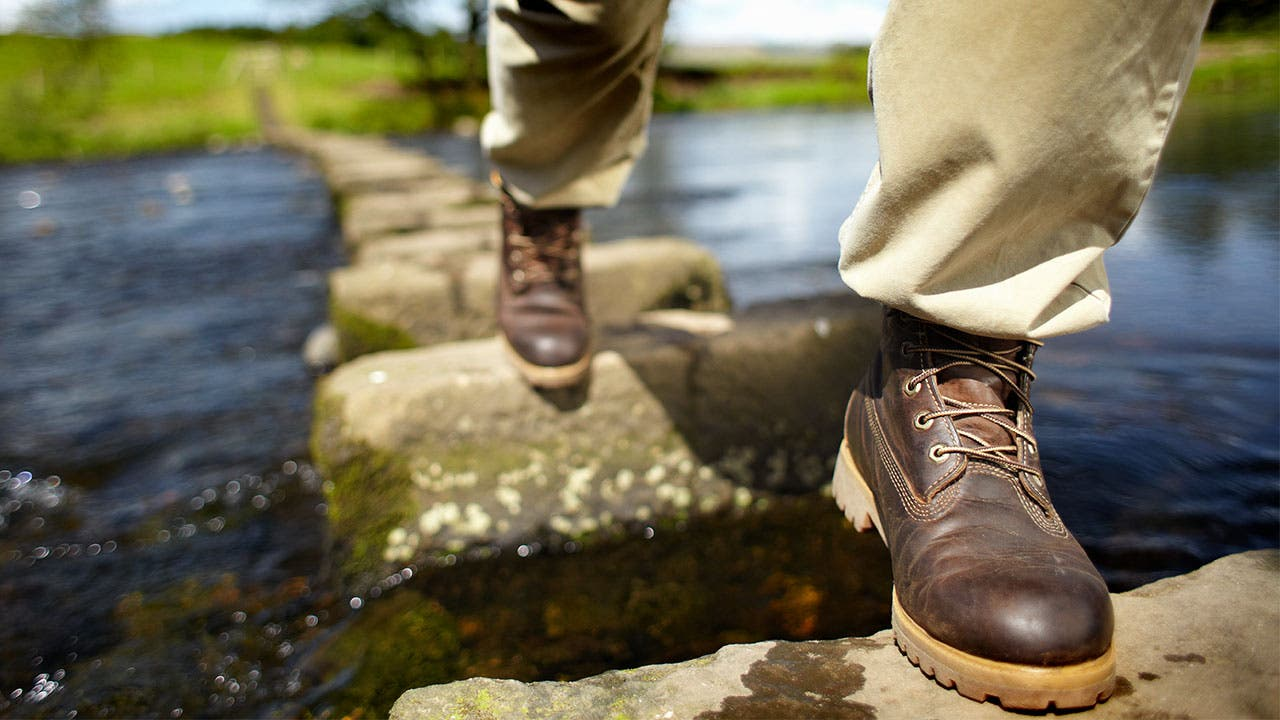 Hiker stepping on stones across a stream of water