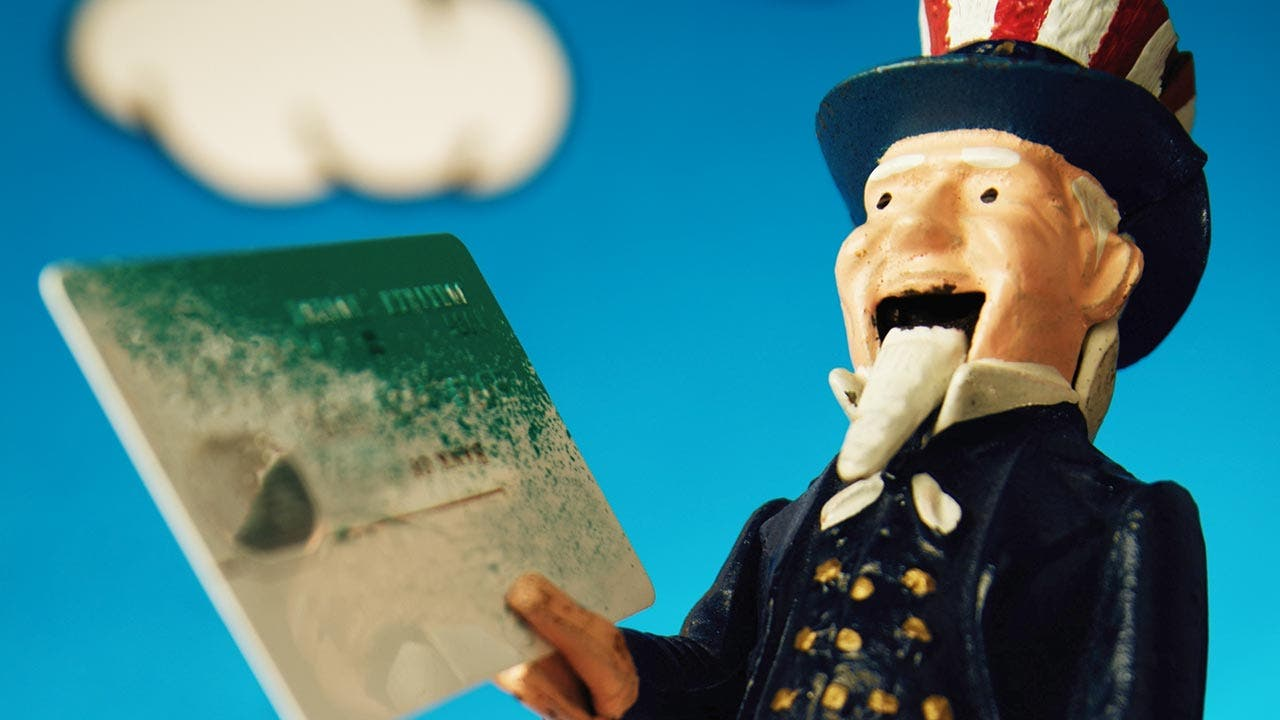 Uncle Sam toy holding a credit card